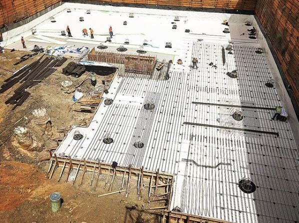 Installing the bottom rebar mat at the lowest level and installing waterproofing on the North end of the parking garage